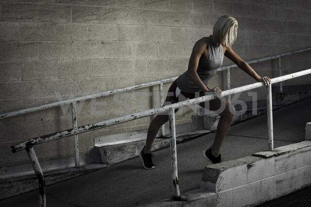 Athlete stretching against handrail - ISF02057