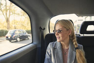 Mid adult woman sitting in back of taxi - CUF08262