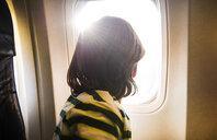 Boy on airplane looking through sunlit airplane window - CUF08280