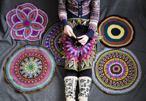 Neck down view of woman sitting on floor crocheting, surrounded by crochet circles - CUF08286
