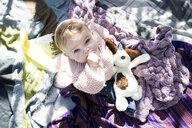 Overhead portrait of baby girl looking up from blanket in garden - CUF08331
