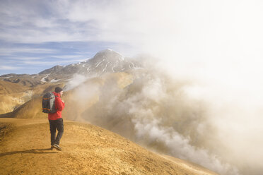Hiker surrounded by geothermal smoke, Kerlingarfjoll, Iceland - CUF08355