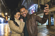 Couple in city at night, taking selfie, using smartphone, Lisbon, Portugal - CUF08367