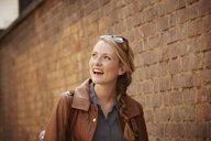 Woman walking along brick wall, London, UK - CUF08463