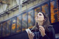 Woman looking at departure information, London, UK - CUF08487