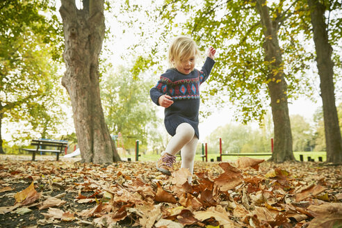 Girl playing in autumn leaves - CUF08505