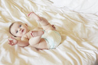 Portrait of cute blue eyed baby girl in diaper lying on bed - CUF08604