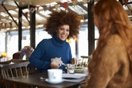 Woman dining in cafe with friend, smiling - CUF08778