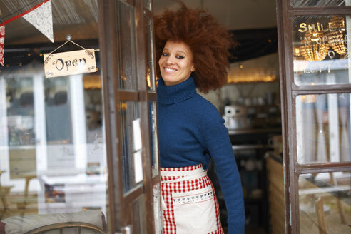 Portrait of small business owner in cafe doorway looking at camera smiling - CUF08787