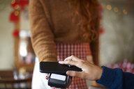 Customer in cafe making contactless payment with mobile phone - CUF08790