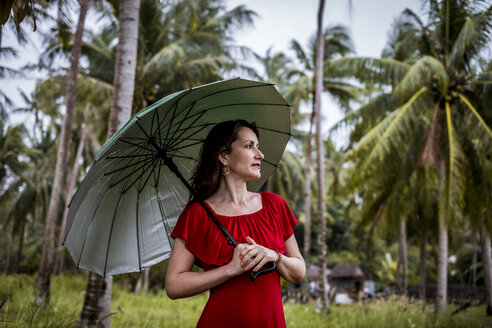 Thailand, Koh Phangan, portrait of woman strolling with umbrella - MMIF00058