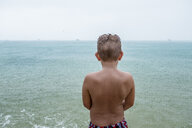 Back view of boy standing in front of the sea on rainy day - MMIF00064