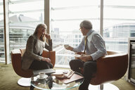 Businessman and businesswoman in coffee area in office, London, UK - CUF08948