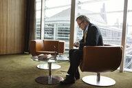Businessman using laptop in coffee area in office, London, UK - CUF08951