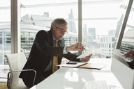 Businessman reading and analysing report, London, UK - CUF08978