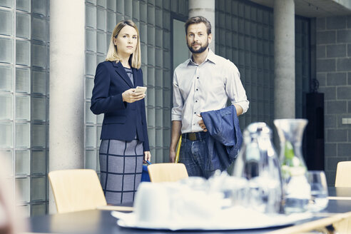 Businesswoman and man standing by boardroom table - CUF09191