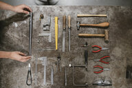 Overhead view of female jeweller's hands laying out hand tools at workbench - CUF09248