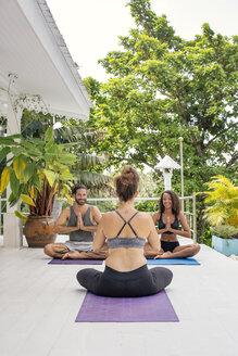 Two women and a man practicing yoga at the poolside - MOMF00411