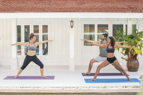 Two women and a man practicing yoga on terrace - MOMF00417