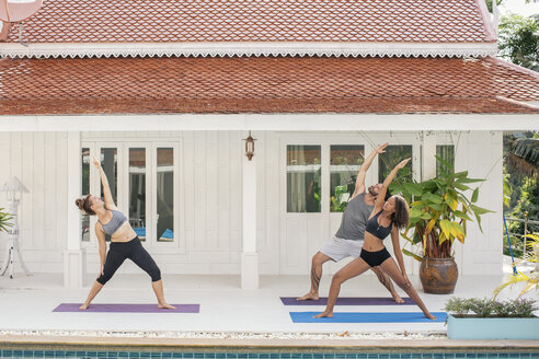 Two women and a man practicing yoga on terrace - MOMF00420