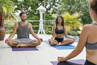 Two women and a man practicing yoga at the poolside - MOMF00423