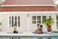 Two women and a man practicing yoga at the poolside - MOMF00426