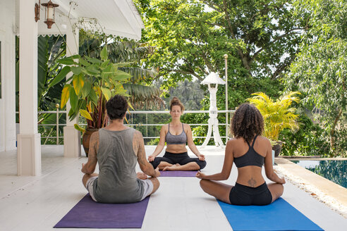 Two women and a man practicing yoga at the poolside - MOMF00429