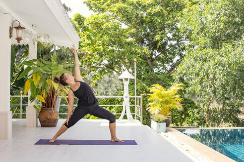 Woman practicing yoga on terrace at the poolside - MOMF00432
