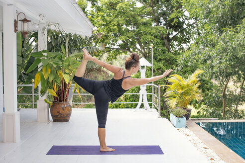 Woman practicing yoga on terrace at the poolside - MOMF00435