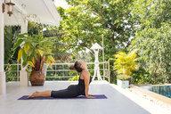 Woman practicing yoga on terrace at the poolside - MOMF00438