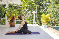 Woman practicing yoga on terrace at the poolside - MOMF00441
