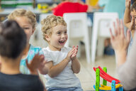 Happy children and pre-school teacher clapping hands in kindergarten - ZEF15442