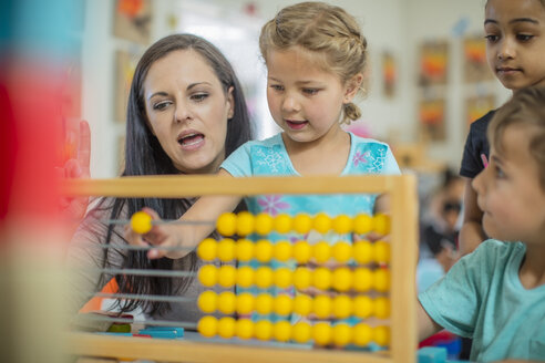 Pre-school teacher with children in kindergarten using abacus - ZEF15445