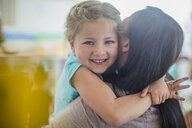 Portrait of smiling girl in kindergarten hugging pre-school teacher - ZEF15448