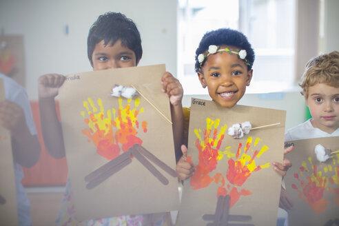 Portrait of smiling children presenting images of fire in kindergarten - ZEF15454