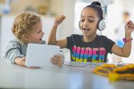 Two girls sharing mini tablet in kindergarten - ZEF15463
