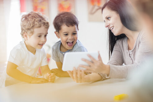 Pre-school teacher showing mini tablet to happy boys in kindergarten - ZEF15466