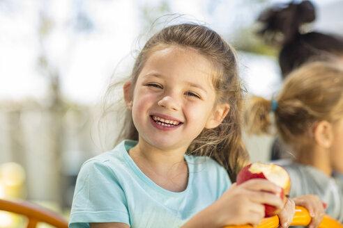 Portrait of happy girl eating an apple in kindergarten - ZEF15472