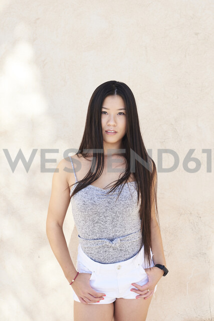 Portrait of pretty asian girl looking at camera with long dark hair - IGGF00495