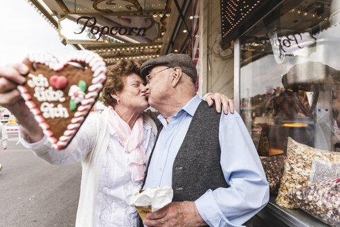 Senior couple with gingerbread heart  kissing on fair - UUF13737