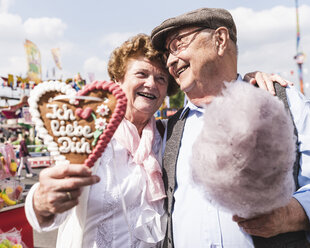 Portrait of happy senior couple with gingerbread heart and cotton candy on fair - UUF13740