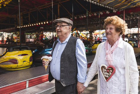 Happy senior couple walking hand in hand on fair - UUF13755
