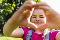 Portrait of smiling girl shaping a heart with her hands in park - UUF13761