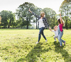 Active happy family walking hand in hand in a park - UUF13770