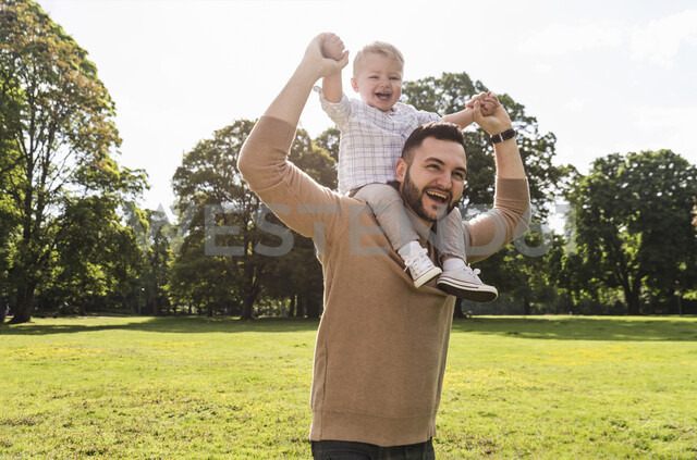 Happy father carrying son on shoulders in a park - UUF13779