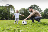 Happy father playing football with son in a park - UUF13785