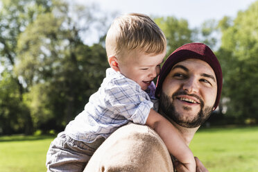 Happy father carrying son on shoulders in a park - UUF13794