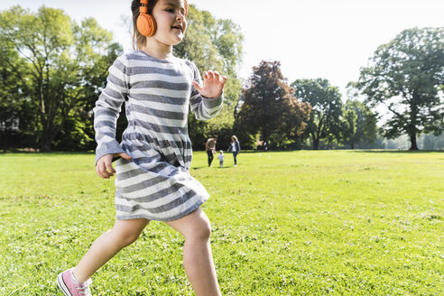 Girl with family in background wearing headphones in a park - UUF13800