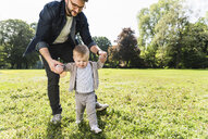 Father helping son to walk in a park - UUF13803