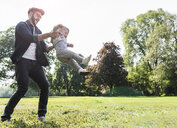 Happy father lifting up son in a park - UUF13806
